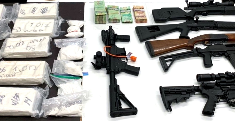 Firearms, cash and drugs seized in a probe conducted by officials in Ontario are seen. (Ontario Provincial Police)