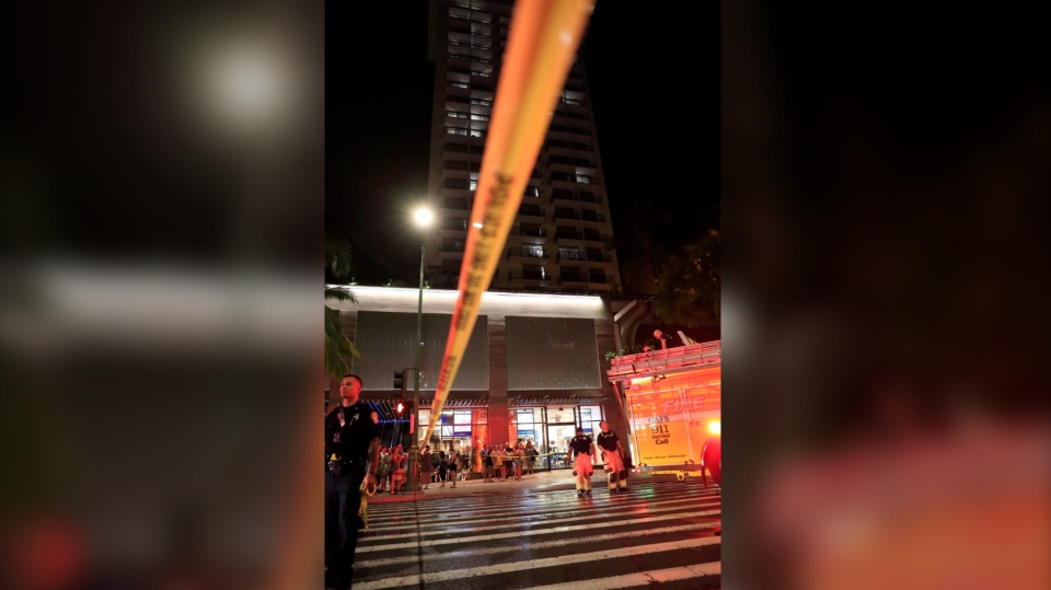 In this Monday, Aug. 5, 2019, photo, police and firefighters respond to a fire the Waikiki Beachcomber by Outrigger hotel in Honolulu. (Jamm Aquino/Honolulu Star Advertiser via AP)