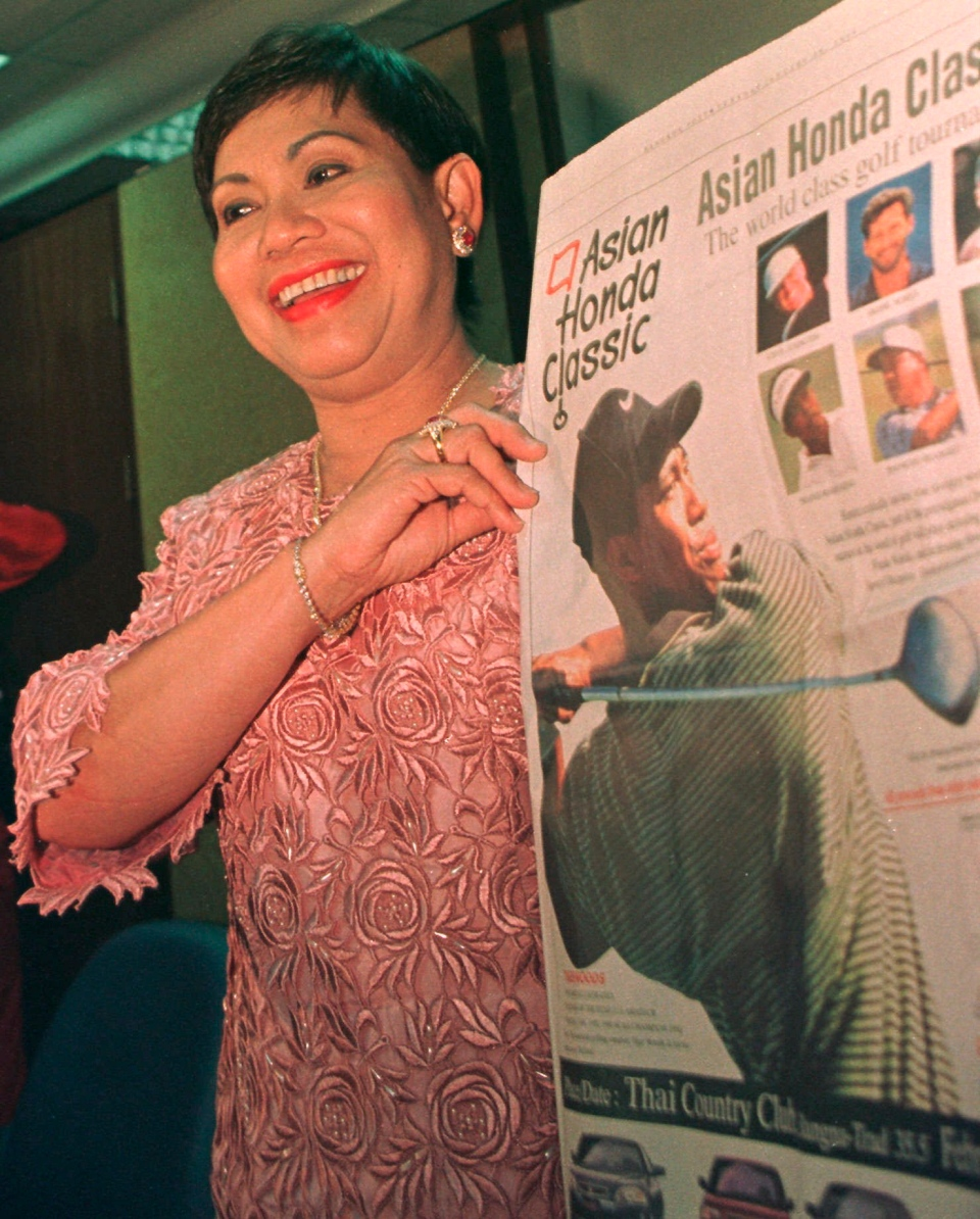FILE - In this Jan. 28, 1997, file photo, Tiger Woods' mother, Kulthida Woods, holds up an advertisement in Bangkok for the Honda Asian Classic which pictures her son. Woods returned to Thailand this summer with his mother and two children. (AP Photo/Charles Dharapak, File)