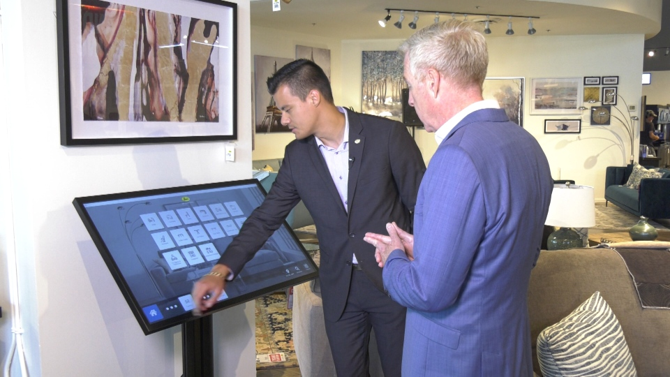 Stuart McBride, Leon's Coquitlam store manager demonstrates new digital features in the company's new concept store.