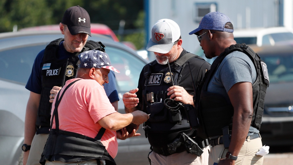 Domingo Candelaria, a registered immigrant, shows federal agents his identification as he prepares to leave the Koch Foods Inc., plant in Morton, Miss., following a raid by U.S. immigration officials, Wednesday, Aug. 7, 2019. (AP Photo/Rogelio V. Solis)