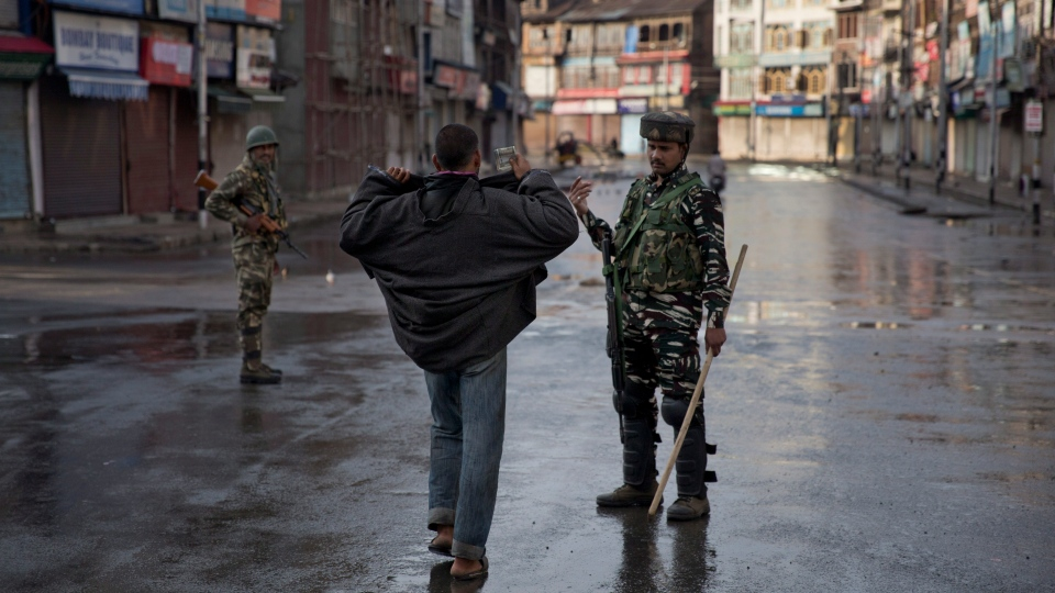 An Indian Paramilitary soldier orders a Kashmiri to lift his robe before frisking him during curfew in Srinagar, Indian controlled Kashmir, Thursday, Aug. 8, 2019. (AP Photo/Dar Yasin)
