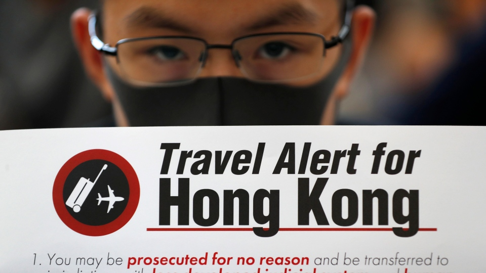 A protester holds up a banner warning of the dangers of traveling to Hong Kong at the airport in Hong Kong on Friday, Aug. 9, 2019. (AP Photo/Vincent Thian)