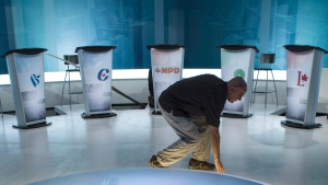 A technician cleans the set in preparation for Thursday night's French language leaders debate Wednesday, September 23, 2015 in Montreal. he official English-language leaders' debate for the fall election is set to conflict with more than 100 planned all-candidates events focused on the environment. THE CANADIAN PRESS/Paul Chiasson