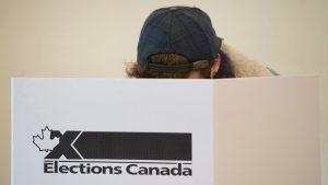A voter marks a ballot behind a privacy barrier in the riding of Vaudreuil-Soulanges, west of Montreal, on election day, Monday, Oct. 19, 2015. THE CANADIAN PRESS/Graham Hughes