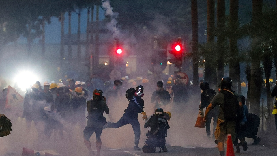 A protester throws a tear gas canister fired by riot policemen during the anti-extradition bill protest in Hong Kong, Sunday, Aug. 11, 2019. (AP Photo/Vincent Thian)
