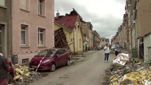 Debris litters the side of streets and roofs are shattered as the clean-up continues Saturday Aug. 10, 2019, after a tornado passed through the area, in the town of Pettingen, Luxembourg, late Friday. (RTL TV via AP)