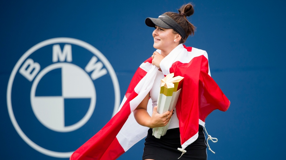 Bianca Andreescu of Canada reacts with the winner's trophy and a Canadian flag after defeating Serena Williams of the United States during Rogers Cup tennis finals tournament action in Toronto on Sunday, August 11, 2019. THE CANADIAN PRESS/Nathan Denette