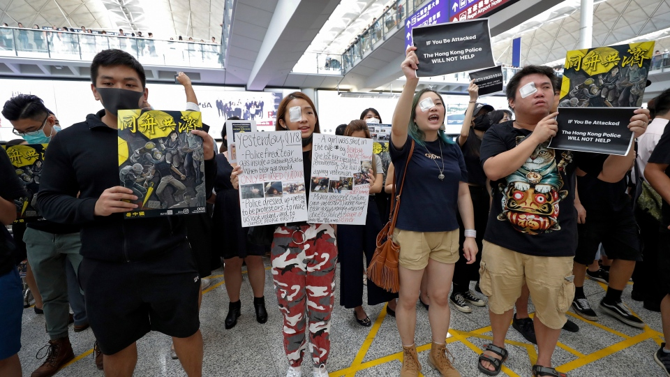 Protesters wear eyepatch during a protest at the arrival hall of the Hong Kong International Airport in Hong Kong, Monday, Aug. 12, 2019. (AP Photo/Vincent Thian)