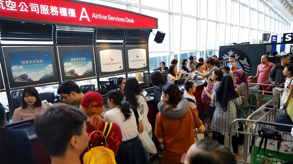 Travelers check their flights information at an airline services desk at the Hong Kong International Airport, Monday, Aug. 12, 2019. (AP Photo/Vincent Thian)