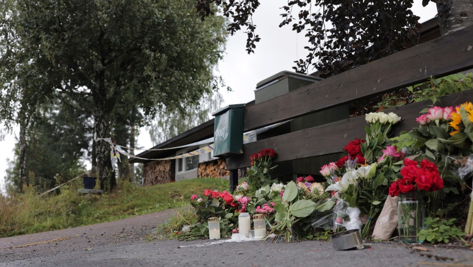 Flowers are left side of the house where the body of the stepsister of a suspected gunman was found, in Baerum, Norway, Monday Aug. 12, 2019. (Orn E. Borgen, NTB scanpix via AP)