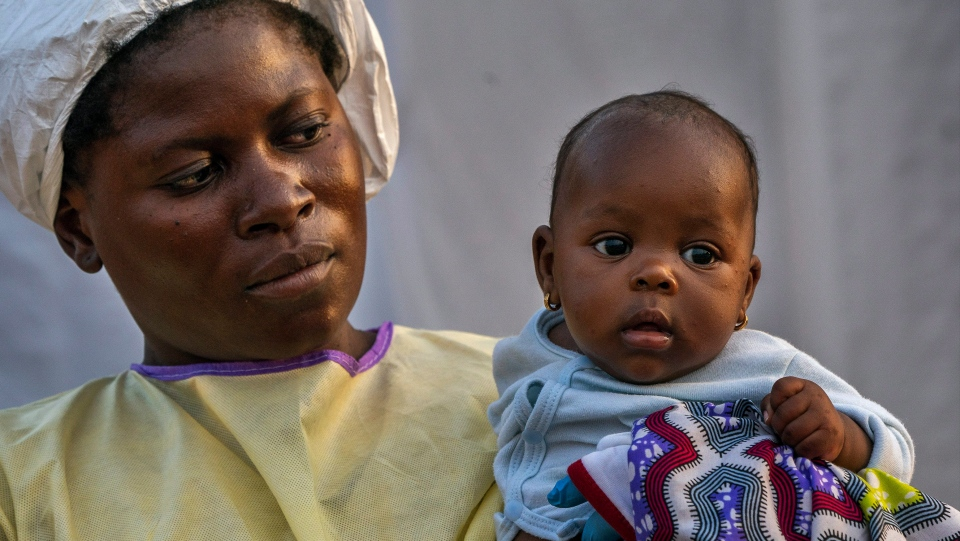 In this Wednesday, July 17, 2019 photo, 2-month-old Lahya Kathembo is carried by a nurse waiting for test results at an Ebola treatment center in Beni, Congo. (AP Photo/Jerome Delay)