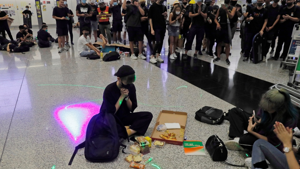 A protester makes a birthday wish during a protest at the Hong Kong International Airport, Monday, Aug. 12, 2019. One of the world's busiest airports canceled all flights after thousands of Hong Kong pro-democracy protesters crowded into the main terminal Monday afternoon. (AP Photo/Kin Cheung)