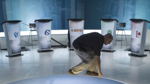 A technician cleans the set in preparation for a leaders debate, Wednesday, September 23, 2015 in Montreal. THE CANADIAN PRESS/Paul Chiasson