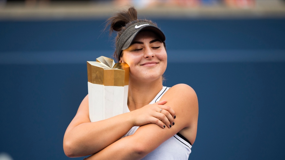 Bianca Andreescu of Canada hugs the winner's trophy after defeating Serena Williams of the United States during Rogers Cup tennis finals tournament action in Toronto on Sunday, August 11, 2019. THE CANADIAN PRESS/Nathan Denette