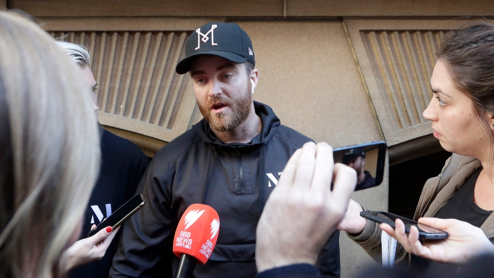 Paul O'Shaughnessy, centre, tells how he and his brother Luke chased down a man who attempted to stab multiple people in Sydney, Australia, Tuesday, Aug. 13, 2019. (AP Photo/Rick Rycroft)