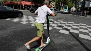 A man rides an electric scooter in Paris, Monday, Aug. 12, 2019. (AP Photo/Lewis Joly)