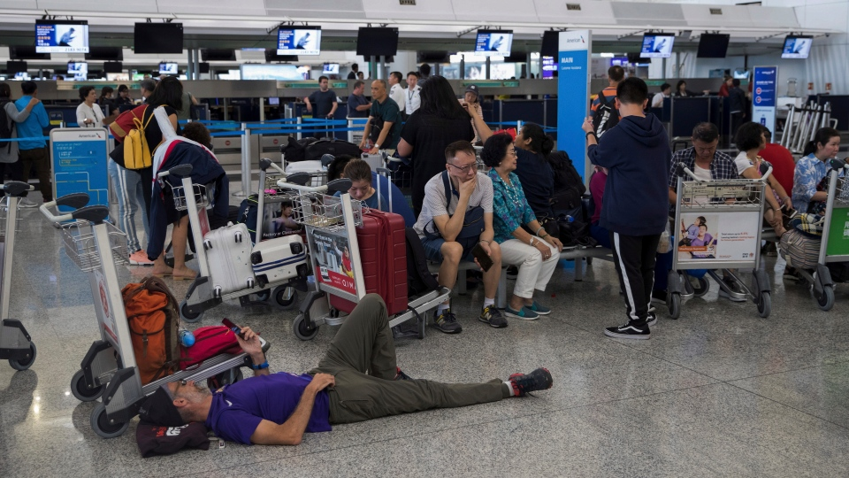 Stranded travelers wait in the departure hall of the Hong Kong International Airport in Hong Kong, Tuesday, Aug. 13, 2019. (AP Photo/Vincent Thian)