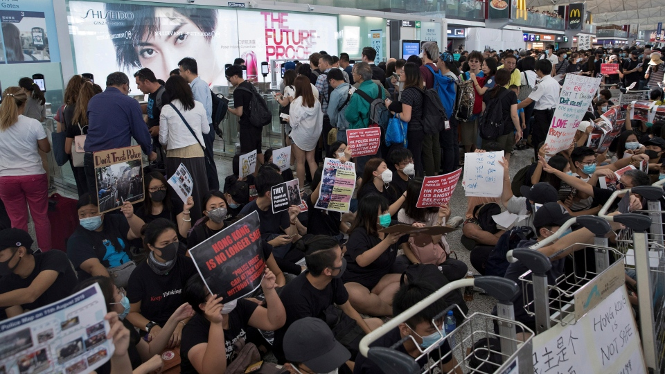Travelers walk past as protesters hold a sit-in rally near the departure gate of the Hong Kong International Airport in Hong Kong, Tuesday, Aug. 13, 2019. (AP Photo/Vincent Thian)