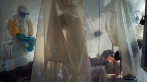 n this July 13, 2019 file photo, health workers wearing protective gear check on a patient isolated in a plastic cube at an Ebola treatment center in Beni, Congo. (AP Photo/Jerome Delay, File)