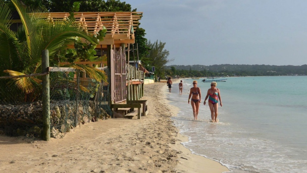 In this Sept. 14, 2014 file photo, sunbathers walk along resort-lined crescent beach in Negril in western Jamaica. THE CANADIAN PRESS/AP-David McFadden