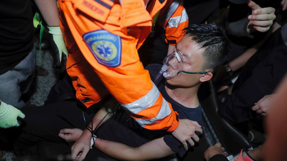 A medical staffer helps a detained man, who protesters claimed was a police officer from mainland China, during a demonstration at the Airport in Hong Kong, Tuesday, Aug. 13, 2019. (AP Photo/Kin Cheung)