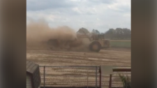 A truck kicks up a cloud of dust