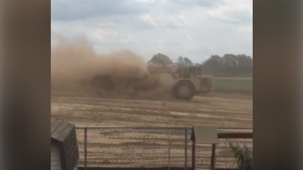 A truck kicks up a cloud of dust