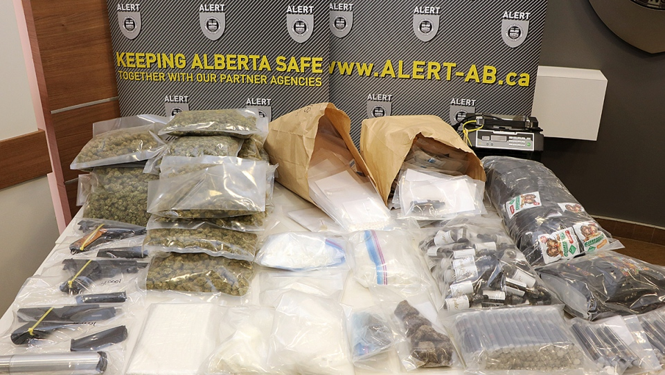 Three stolen handguns and more than $560,000 worth of drugs and cash have been seized after ALERT searched two Edmonton homes.