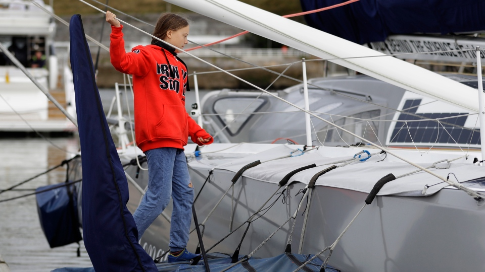 Greta Thunberg climbs onto the boat Malizia as it is moored in Plymouth, England Tuesday, Aug. 13, 2019. (AP Photo/Kirsty Wigglesworth)