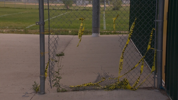 Caution tape up around a hole made in the fence at