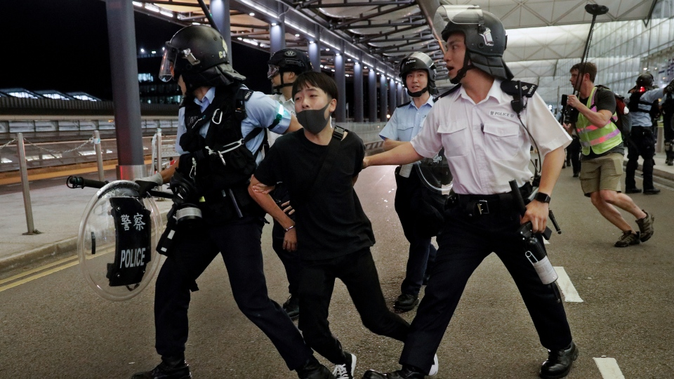 Policemen arrest a protester during a clash at the Airport in Hong Kong, Tuesday, Aug. 13, 2019. (AP Photo/Vincent Yu)