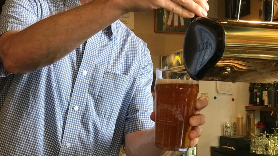 Grant Frew, the bar manager of Bushwakker Brewpub, pours a beer at their location in Regina. (Stefanie Davis/CTV News)