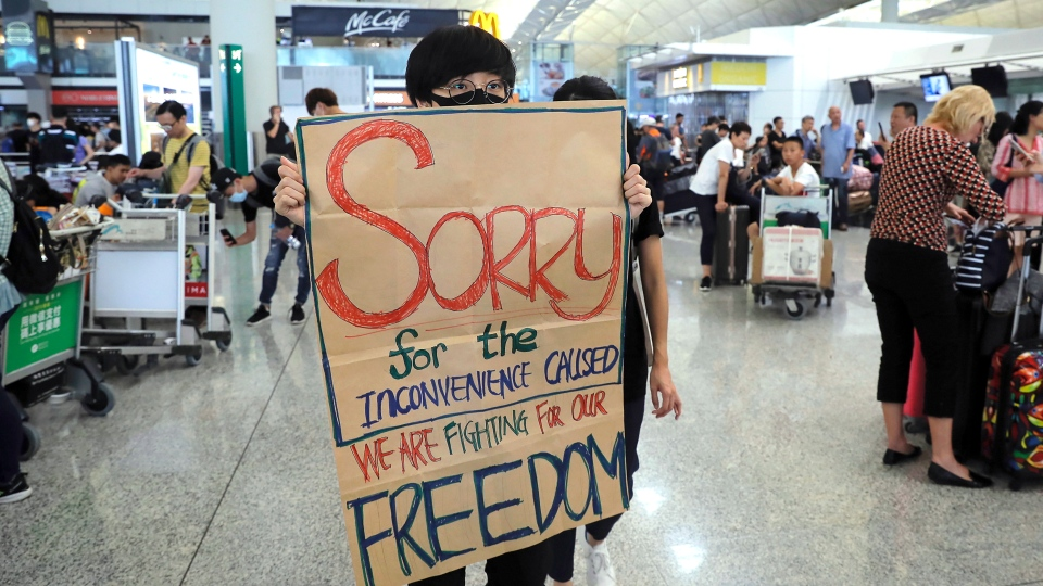 A protester shows a placard to stranded travelers during a demonstration at the Airport in Hong Kong, Tuesday, Aug. 13, 2019.  (AP Photo/Kin Cheung)