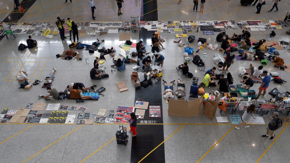 Protesters continue their sit-in rally at the airport in Hong Kong, Wednesday, Aug. 14, 2019. (AP Photo/Vincent Thian)