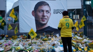 In this Wednesday, Jan. 30, 2019, file photo, a Nantes soccer team supporters stops by a poster of Argentinian player Emiliano Sala outside La Beaujoire stadium in Nantes, western France. (AP Photo/Thibault Camus, File)