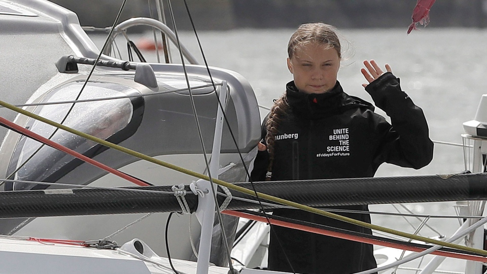 Climate change activist Greta Thunberg waves from the Malizia II boat in Plymouth, England, on Aug. 14, 2019. (Kirsty Wigglesworth / AP)