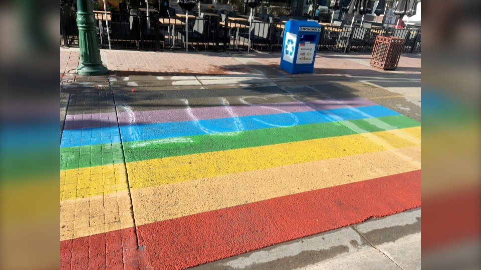 The word 'lust' appears to have been spray painted on the pride crosswalk in downtown Calgary.
