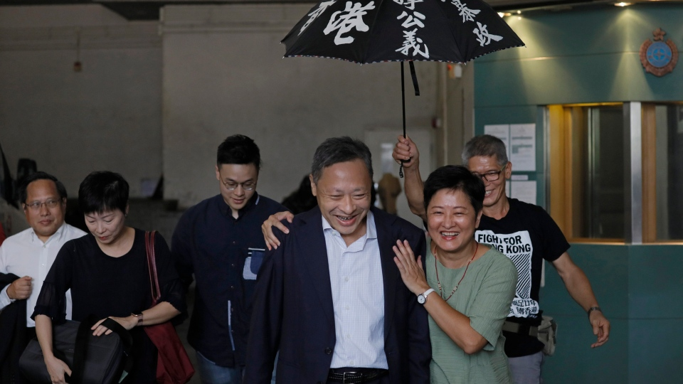 Occupy Central leader Benny Tai, front left, is accompanied by pro-democracy lawmaker Helena Wong, family members and supporters as he leaves the High Court in Hong Kong Thursday, Aug. 15, 2019. (AP Photo/Vincent Yu)