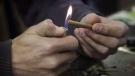 A man lights a marijuana cigarette at on April 25, 2017. THE CANADIAN PRESS/Joe Mahoney