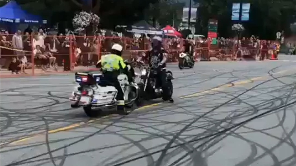 A motorcycle stunt involving an RCMP officer is seen in this image posted to social media. (Derek Lewers / Twitter)
