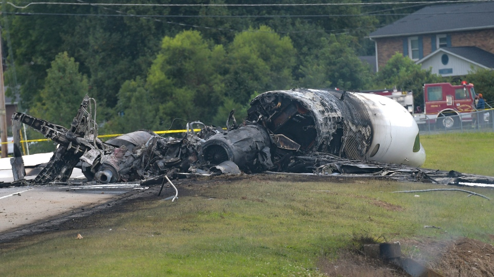 The burned remains of a plane that was carrying NASCAR television analyst and former driver Dale Earnhardt Jr. lie near a runway Thursday, Aug. 15, 2019, in Elizabethton, Tenn. (Earl Neikirk/Bristol Herald Courier via AP)