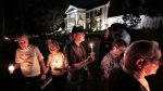 A procession of fans passes by Graceland while visiting Elvis Presley's grave during the annual Elvis Week candlelight vigil to honor the 42nd anniversary of the rock 'n' roll icon's death, Thursday, Aug. 15, 2019, in Memphis, Tenn. (Jim Weber/Daily Memphian via AP)