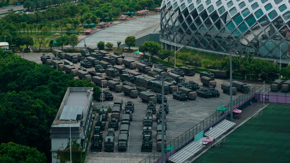 Armored vehicles and troop trucks are parked in a lot by Shenzhen Bay Stadium in Shenzhen, China Friday, Aug. 16, 2019. (AP Photo/Dake Kang)