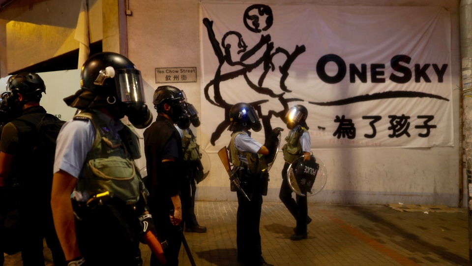 Policemen in riot gear stand guard during a face off with protesters in Hong Kong, Wednesday, Aug. 14, 2019. (AP Photo/Vincent Yu)