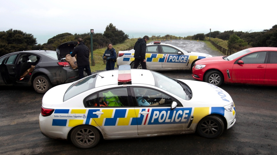 Police collect and photograph evidence in the carpark of the Te Toto Gorge lookout on Whaanga Rd, south of Raglan, New Zealand, Friday, Aug. 16, 2019. (Alan Gibson/New Zealand Herald via AP)