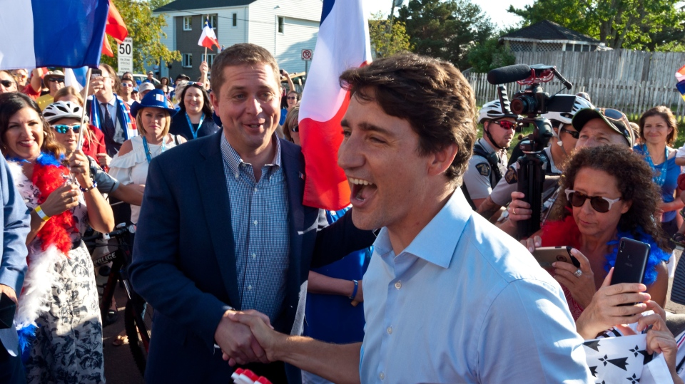 Prime Minister Justin Trudeau shakes hands with Conservative Leader Andrew Scheer while walking with the crowd during the Tintamarre in celebration of the National Acadian Day and World Acadian Congress in Dieppe, N.B., Thursday, Aug. 15, 2019. THE CANADIAN PRESS/Marc Grandmaison