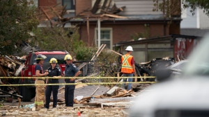 Fire officials investigate the scene of a house explosion caused by a car crashing into a house in London, Ont., Thursday, August 15, 2019. THE CANADIAN PRESS/Geoff Robins