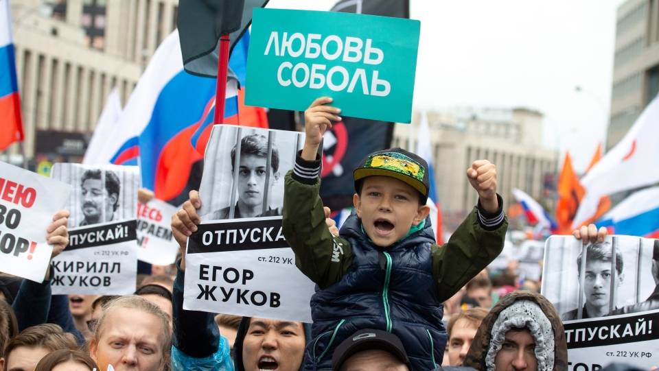 In this photo taken on Aug. 10, 2019, people with posters show portraits of detained protesters and a boy with a poster reads Lyubov Sobol react during a protest in Moscow, Russia. This summer's wave of opposition protests has pushed Sobol to the forefront of the Russian political scene. (AP Photo/Alexander Zemlianichenko, File)