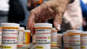 Family and friends who have lost loved ones to OxyContin and opioid overdoses leave pill bottles in protest outside the headquarters of Purdue Pharma, which is owned by the Sackler family, in Stamford, Conn., on Aug. 17, 2018. (Jessica Hill / AP)